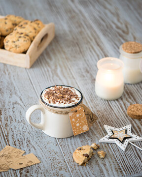 a cup of hot coffee sprinkled with chocolate with cookies