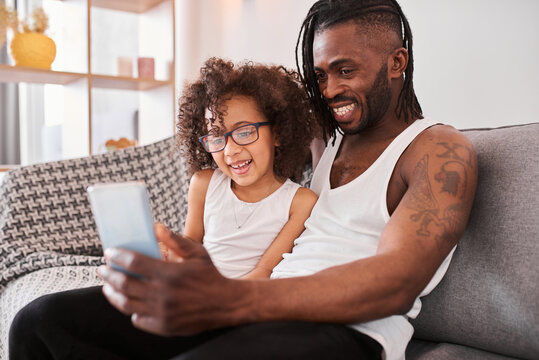 Man making selfie with his curly daughter while sitting at the sofa at home