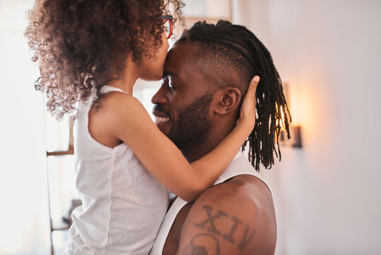 Daughter smiling, kissing at the forehead her father and hugging him