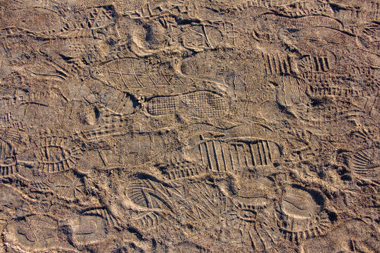 Many shoe sole footprints on sand. Walk path. Holiday concept
