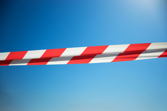 Red and White Lines of barrier tape on a blue  background. Do not cross, closed passage, ban, concept.