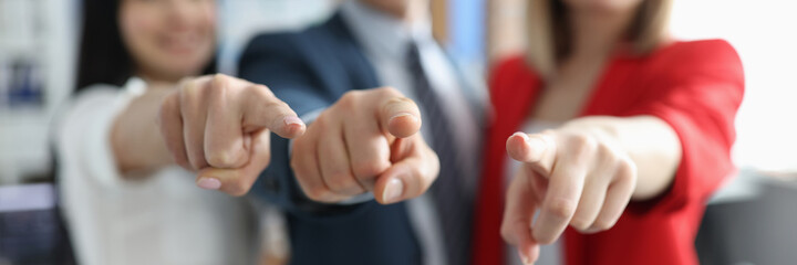 Successful business partners pointing finger in front of them closeup