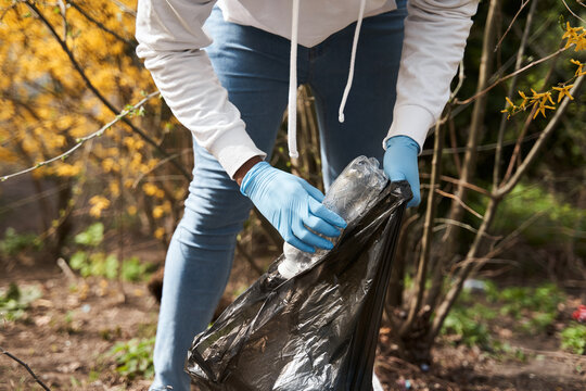 Volunteer helping to pick up waste by garbage bags in park