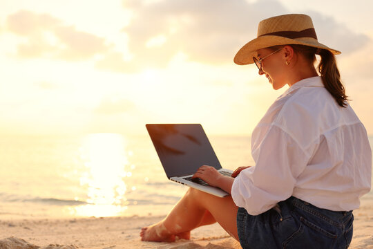 Young female freelancer wearing straw hat working on laptop while sitting on tropical beach at sunset