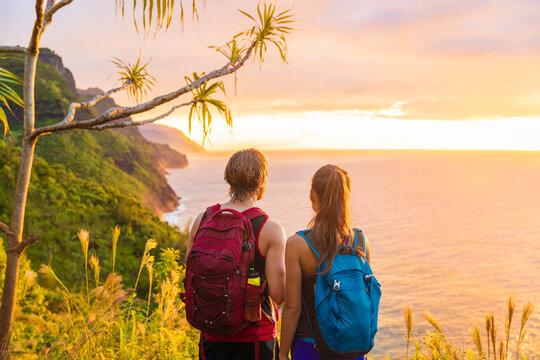 Hawaii hiking hikers hiking on Kalalau trail watching sunset from Na Pali Coast. Tourists couple with backpacks walking outdoor in Kauai island. Summer travel adventure active lifestyle.