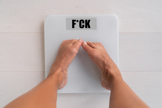 Funny weight gain woman weighting herself on weight balance scale worried scared of screen in bathroom floor needing help to lose fat - obesity after the christmas holidays.