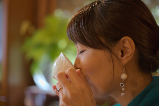 An Asian woman sipping a cup of coffee in a cafe.