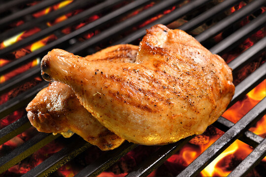 Grilled chicken thighs on the flaming grill