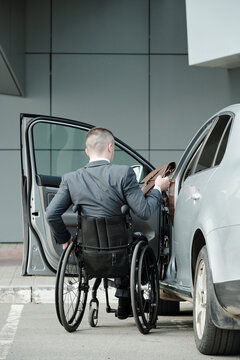 Back view of handicapped businessman in suit going to get into his car