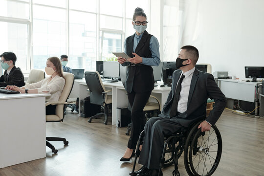 Two colleagues in protective masks interacting while moving along open space office