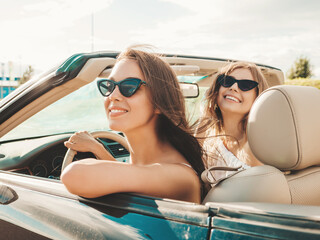 Fototapeta Portrait of two young beautiful and smiling hipster female in convertible car. Sexy carefree women driving cabriolet. Positive models riding and having fun in sunglasses outdoors. Enjoying summer days obraz