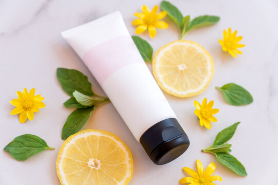 beauty spa medical skincare and cosmetic lotion tube cream packaging product on white marble background with lemon slices. fruit vitamin c herb extract