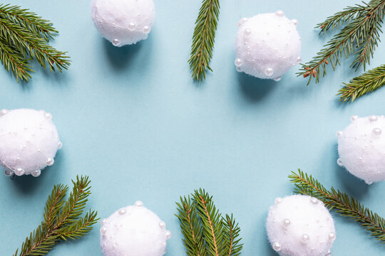 Christmas minimal concept - Christmas composition with fir branches and white baubles. Horizontal frame, flat lay, view from above. Pastel blue background with copy space