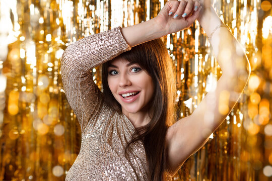 birthday or New Year's eve party. Young beautiful brunette in a gold dress