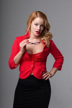 Sensual blonde woman in red biting eyeglasses