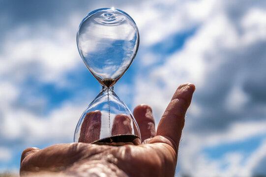 Ablaufende Zeit zum Schutz des Klimas dargestellt mit einer Sanduhr vor dem Himmel