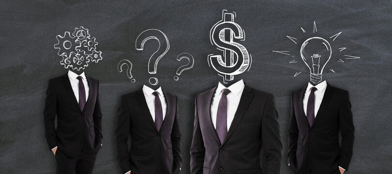 Idea and financial development concept. Headless businessmen in suits standing on chalkboard background with symbol scribbles.