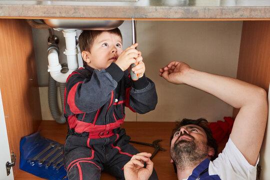 Kind hilft bei der Installation einer Spüle