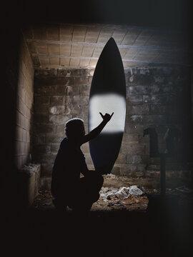 Man showing shaka gesture in darkness near surf board
