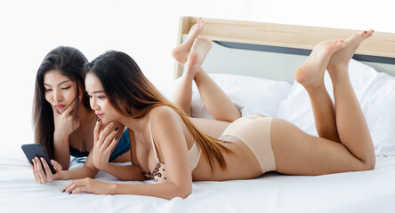 Fototapeta couple of beautiful Asian young sexy girl with seductive underwear lying down together on white bed happily playing with smile to their social media from smartphone with intimate pose. obraz