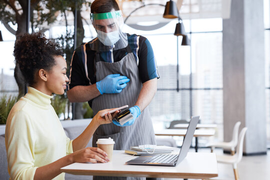 Portrait of waiter wearing face shield and gloves while serving customer in cafe with covid safety measures, copy space