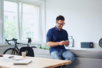 Fototapeta Man using phone having break from work from home obraz