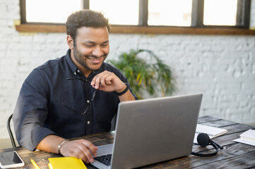 Obraz Optimistic indian mixed race man using laptop, male employee in smart casual shirt take off eyewear, watching at the monitor and smiling - fototapety do salonu