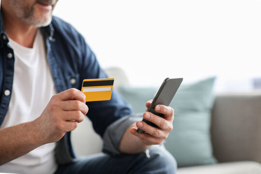Unrecognizable man using smartphone and holding credit card