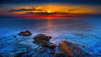 Fototapeta Skały na wybrzeżu morza Adriatyckiego w Grecji o wschodzie słońca obraz