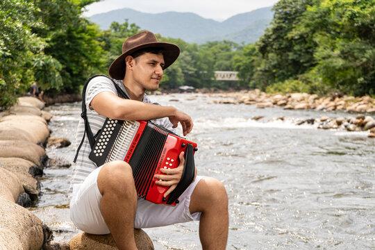 Joven tocando el acordeon a orillas del rio guatapuri en valledupar