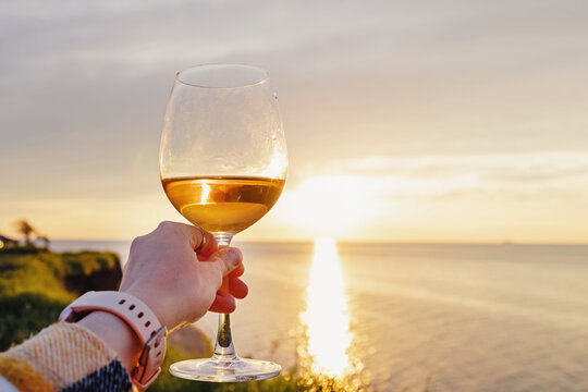 Woman hand holding a glass of rose wine at sunset