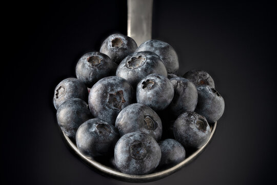 Fresh blueberries on a stainless steel spoon.