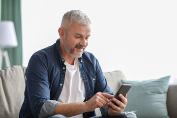 Fototapeta Smiling senior man using smartphone at home obraz