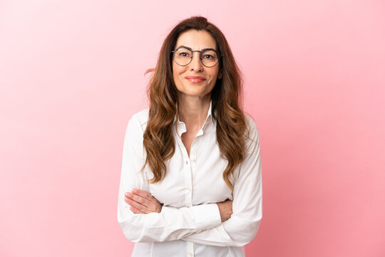 Middle aged caucasian woman isolated on pink background keeping the arms crossed in frontal position