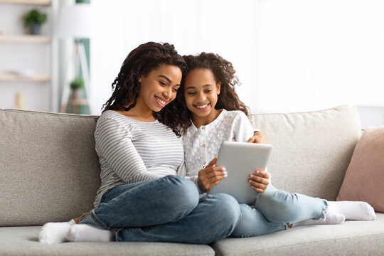 Cute african american mother and kid using digital tablet together