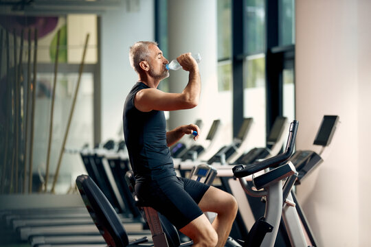 Mature sportsman having water break while exercising on stationary bike in a gym.