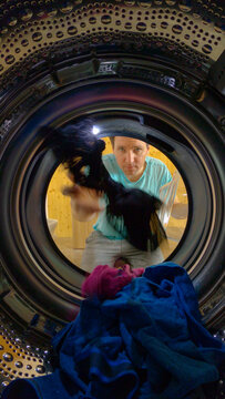 VERTICAL: Male doing housework over the weekend is loading up washing machine.