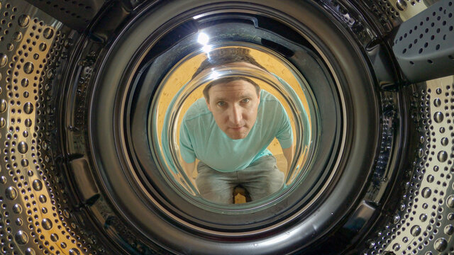 PORTAIT: Caucasian man doing chores on the weekend looks into the empty washer.