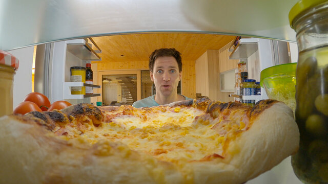 PORTRAIT: Young man is surprised to see leftover pizza after opening his fridge.