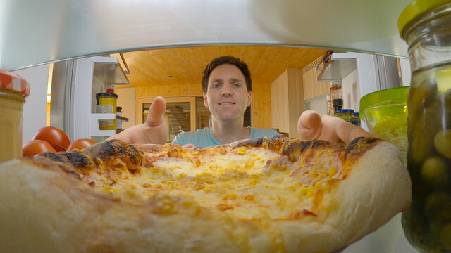 CLOSE UP: Man on diet gives into temptation and takes a pizza out of his fridge.