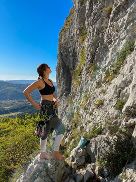 VERTICAL: Young female rock-climber observes the cliff before climbing it.