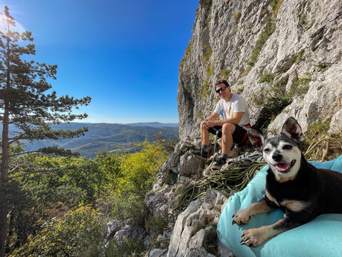 COPY SPACE: Climber and his miniature pinscher resting during fun climbing trip.