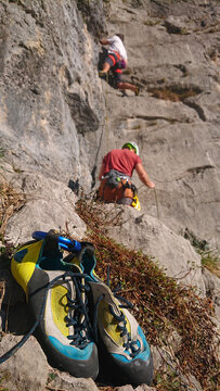 VERTICAL: Rock-climber's shoes lie on the ground as others scale the rocky wall.