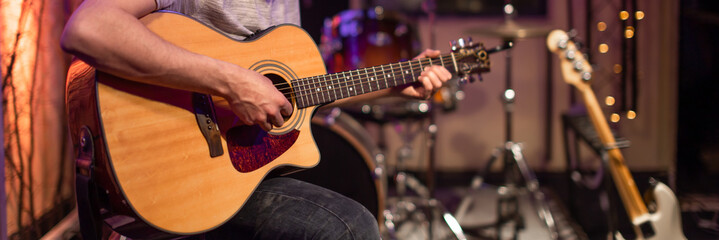 A man plays an acoustic guitar in a recording Studio. A room for musicians ' rehearsals, with a...