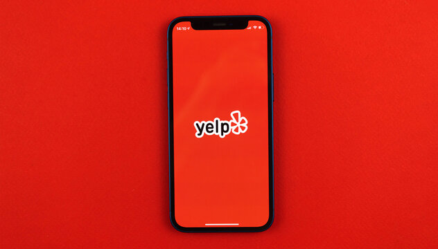 Kharkov, Ukraine - May 28, 2021: Yelp application logo on Apple iPhone 12 screen with red background, Yelp app social network and services