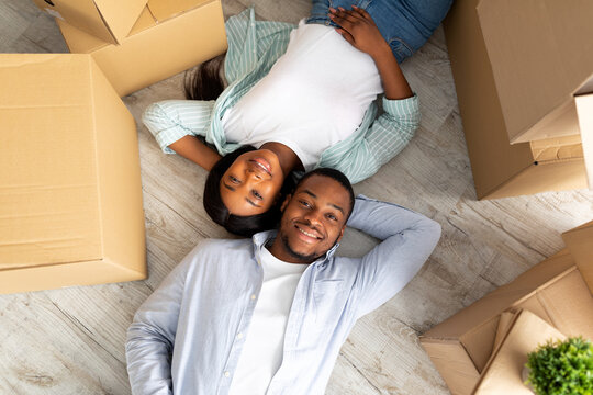 Loving african american couple lying among cardboard boxes on floor of their new apartment, top view
