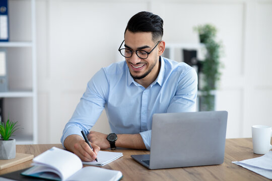 Arab male entrepreneur writing down information during online business meeting at modern office
