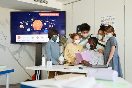 Portrait of diverse group of children and teacher wearing masks in school classroom, covid safety measures, copy space