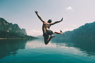 Fototapeta Man jumping with joy by a lake obraz