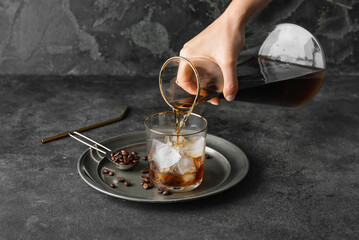 Obraz Pouring of cold brew coffee from jug into glass on grunge background - fototapety do salonu
